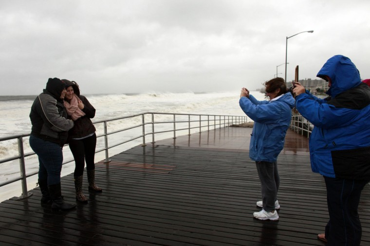 October 29, 2012: People pose for pictures on the Rockaway Beach Boulevard ahead of Hurricane Sandy in the Queens borough of New York City. (Allison Joyce/Getty Images)