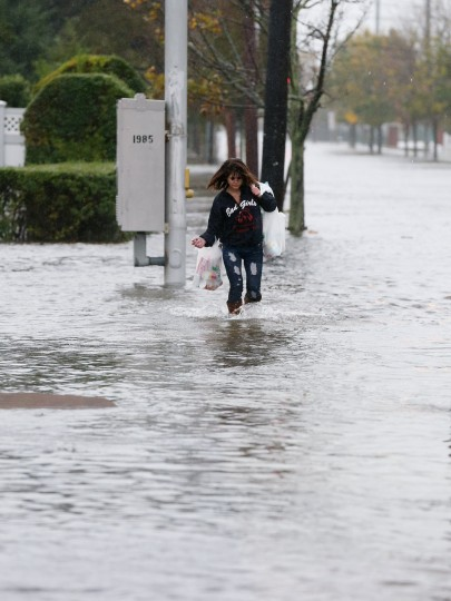 October 29, 2012: Maria Petillo of Freeport makes her way up a flooded Guy Lomardo Avenue as high tide and winds from Hurricane Sandy combine to flood the area in Freeport, New York. (Bruce Bennett/Getty Images)