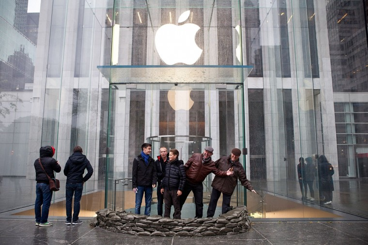 October 29, 2012: People pose outside the sandbaged enterence of the closed Apple Store on Fifth Avenue as Hurricane Sandy moves closer to the area in New York. (Andrew Burton/Getty Images)