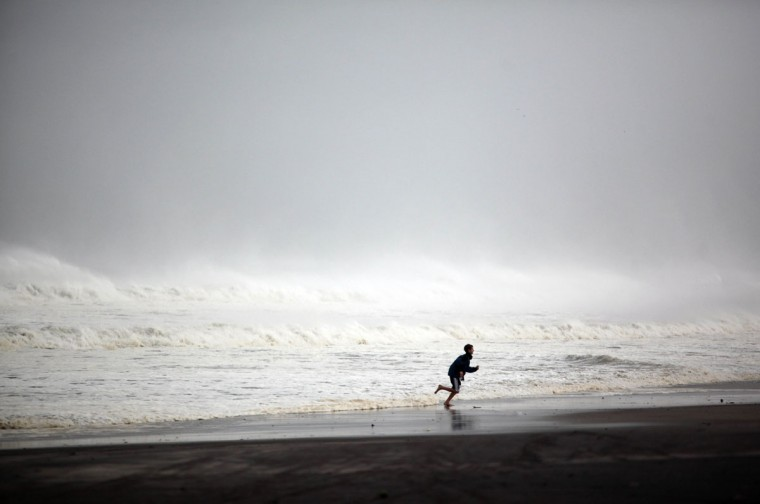 October 29, 2012: A young boy runs along Rockaway Beach as Hurricane Sandy begins to affect the area in the Queens borough of New York City. (Allison Joyce/Getty Images)