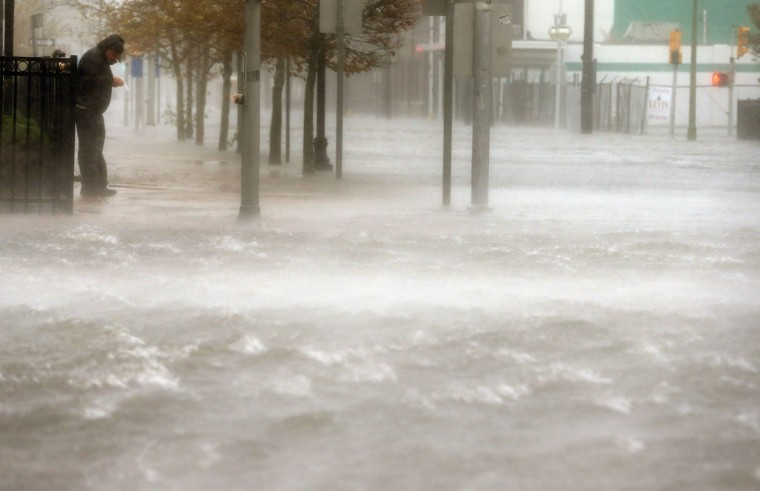 October 29, 2012: A man stands on a dry patch of sidewalk on a flooded street as Hurricane Sandy moves up the coast in Atlantic City, New Jersey. (Mario Tama/Getty Images)