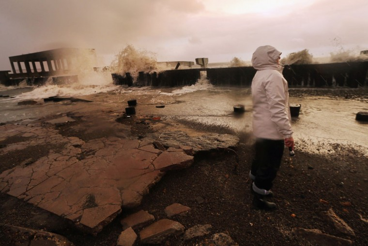 October 30, 2012: Resident Kim Johnson inspects the area around her apartment building which flooded and destroyed large sections of an old boardwalk in Atlantic City, New Jersey. (Mario Tama/Getty Images)