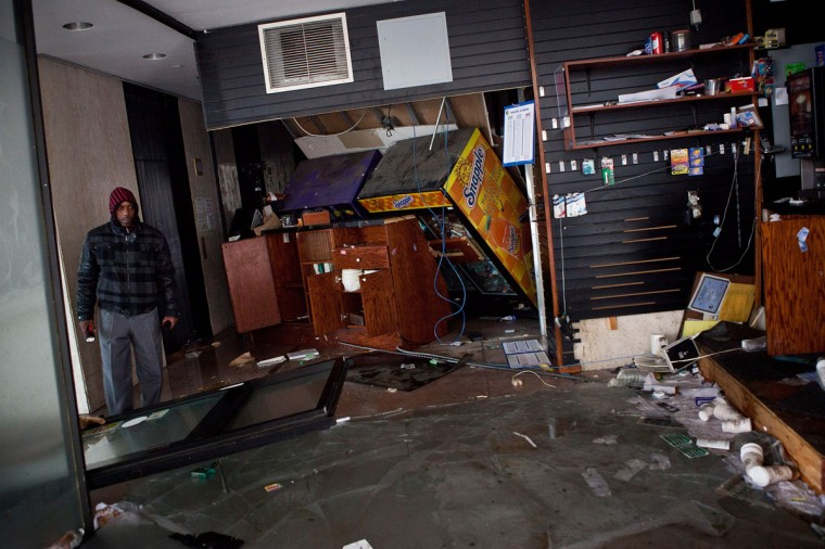 October 30, 2012: A man surveys the remains of a flooded store following Hurricaine Sandy in the Financial District of New York, United States. (Andrew Burton/Getty Images)