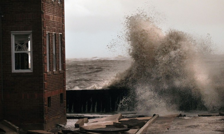 October 30, 2012: Waves break next to an apartment building which flooded from Hurricane Sandy in Atlantic City, New Jersey. (Mario Tama/Getty Images)