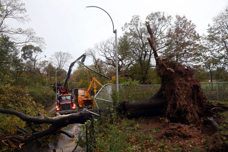 October 30, 2012: Workers clear a downed tree blocking East 96th street in Central Park the morning after Hurricane Sandy in New York City. (Michael Heiman/Getty Images)