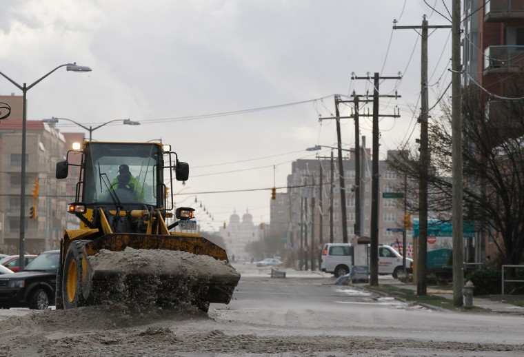 A member of the cleanup crew removes beach sand that was left on the streets after Hurricane Sandy on October 30, 2012 in Long Beach, New York. The storm has claimed at least 40 lives in the United States, and has caused massive flooding across much of the Atlantic seaboard. US President Barack Obama has declared the situation a 'major disaster' for large areas of the US East Coast including New York City. (Mike Stobe/Getty Images)
