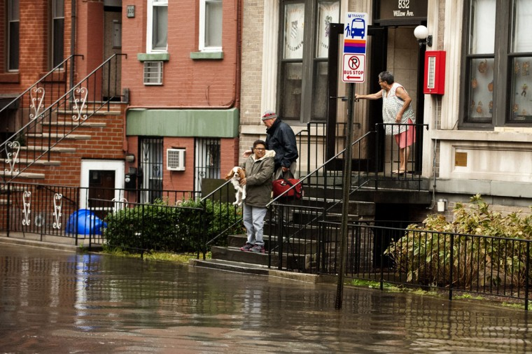 Residents stand in front of a building on a flooded street in Hoboken, N.J. after Hurricane Sandy. The storm caused massive flooding across much of the Atlantic seaboard, leaving millions of people without power. (Michael Bocchieri/Getty Images)