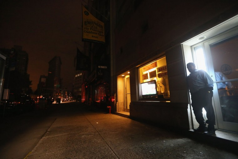 A man stands in a doorway of a building with power on Fifth Avenue in a section of Manhattan still in a blackout in New York City. The storm caused massive flooding across much of the Atlantic seaboard, leaving millions of people without power. (Mario Tama/Getty Images)