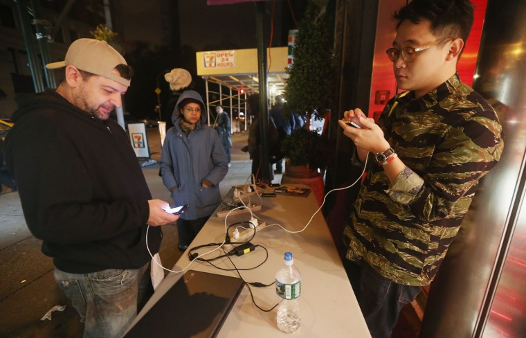 People charge their devices at a free charging station offered by a 7-11 store in an area with power in Manhattan following Hurricane Sandy. The storm caused massive flooding across much of the Atlantic seaboard and left millions of people without power. (Mario Tama/Getty Images)