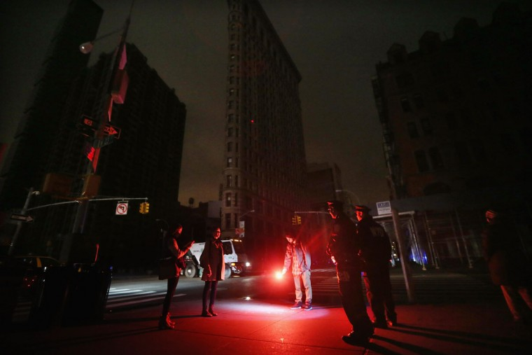 Police gather to tell a man to put out the road flare was using as an impromptu flashlight while walking with friends during a power outage in New York caused by the remnants of Hurricane Sandy. (Photo by Mario Tama/Getty Images)