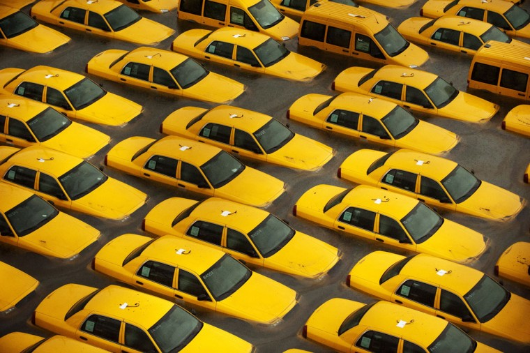 Taxis sit in a flooded lot following the impact of Hurricane Sandy in Hoboken, N.J. With New York's tunnels flooded and the subway system closed, commuters have been forced to rethink how they will make their way to work in the New York area. (Michael Bocchieri/Getty Images)