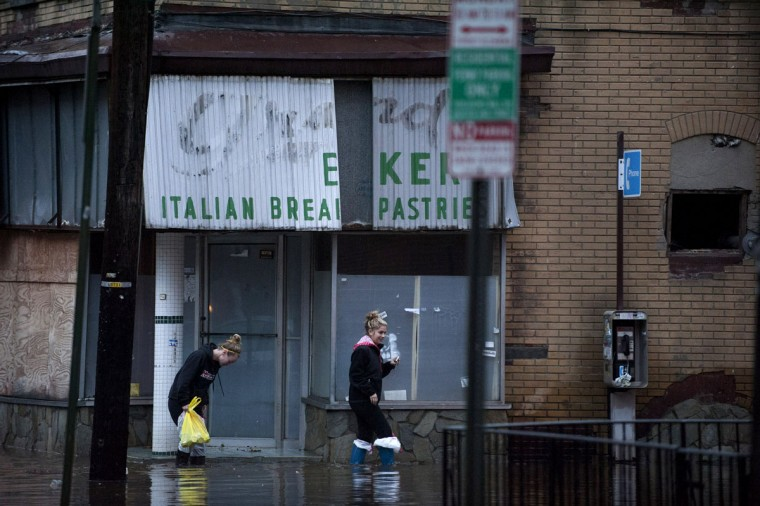 Two women walk along a street flooded with water from Hurricane Sandy in Hoboken, N.J. The storm caused massive flooding across much of the Atlantic seaboard, leaving millions of people without power. (Michael Bocchieri/Getty Images)