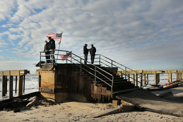 Residents stand on the remains of part of the historic Rockaway boardwalk after large parts of it were washed away during Hurricane Sandy in the Brooklyn borough of New York City. With millions of homes and businesses without power, the eastern U.S. is attempting to recover from the affects of floods, fires and power outages. (Spencer Platt/Getty Images)