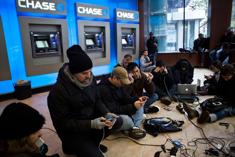 "People crowd into a Chase Bank ATM kiosk to charge phones and laptops at 40th Street and 3rd Avenue, one block north of where power has gone out, on October 31, 2012 in New York City. ""This is the modern campfire,"" one man said. (Andrew Burton/Getty Images)"