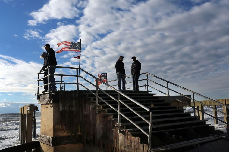 Residents stand on the remains of part of the historic Rockaway boardwalk after large parts of it were washed away during Hurricane Sandy on October 31, 2012 in the Brooklyn borough of New York City. (Spencer Platt/Getty Images)