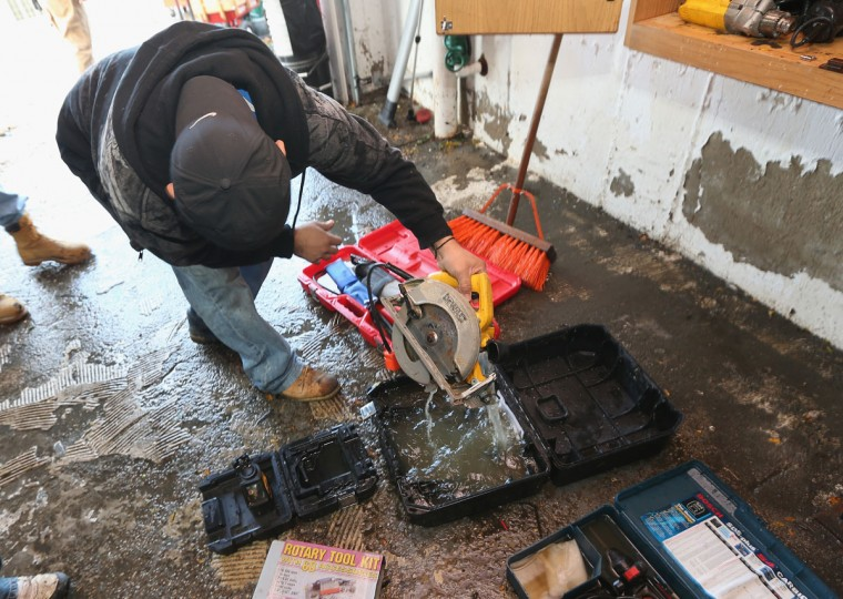 Mike Saracco checks out his water-logged power tools in his garage caused by Hurricane Sandy on Narraganset Avenue on October 31, 2012 in Seaford, New York. (Bruce Bennett/Getty Images)