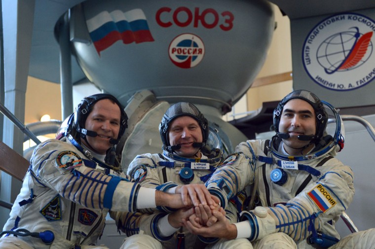 September 21, 2012: Crew members of the next expedition to the International Space Station (ISS), US astronaut Kevin Ford (L) joins hands with crew members Russian cosmonauts Oleg Novitskiy (C) and Evgeny Tarelkin (R) in front of a mock-up of a Soyuz TMA space craft before their final preflight practical examination at the Cosmonaut Training Centre in Star City, outside Moscow. (Kirill Kudryavtsev/AFP/GettyImages)