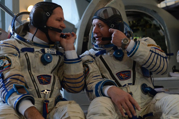 September 21, 2012: Crew members of the next expedition to the International Space Station (ISS), US astronaut Kevin Ford and Russian cosmonauts Oleg Novitskiy speak as they sit in front of a mock-up of a Soyuz TMA space craft before their final preflight practical examination at the Cosmonaut Training Centre in Star City, outside Moscow. (Kirill Kudryavtsev/AFP/GettyImages)
