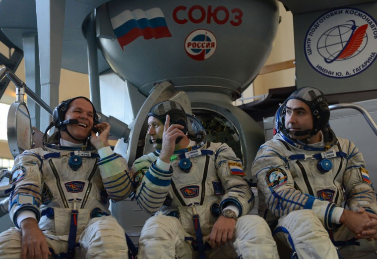 September 21, 2012: Crew members of the next expedition to the International Space Station (ISS), US astronaut Kevin Ford, Russian cosmonauts Oleg Novitskiy and Evgeny Tarelkin, speak as they sit in front of a mock-up of a Soyuz TMA space craft before their final preflight practical examination at the Cosmonaut Training Centre in Star City, outside Moscow. (Kirill Kudryavtsev/AFP/GettyImages)