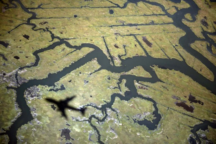 The shadow of Air Force One carrying U.S. President Barack Obama flies over marshland while on approach to John F. Kennedy International Airport September 24, 2012 in New York. (Brendan Smialowski/AFP/Getty Images)