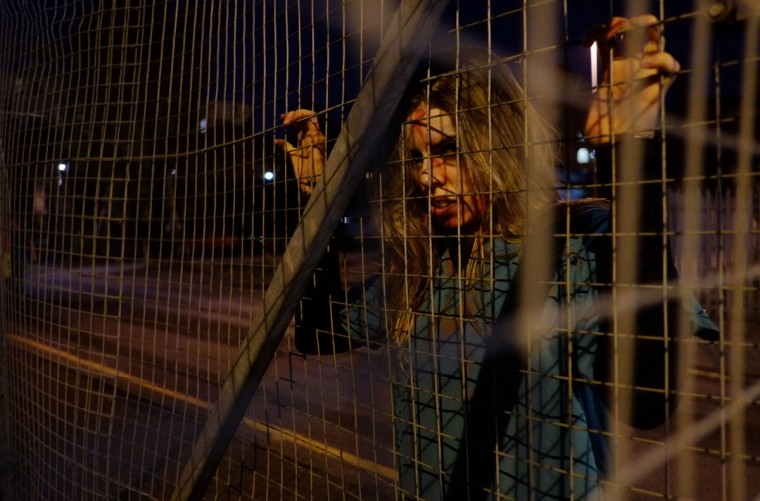 "A ""zombie"" actor waits for participants during the last of three nights of the zombie chase game ""2.8 Hours Later"" in central Manchester, northern England on September 29. The game sees small groups of six to eight people attempt to make their way between points in a major city, meeting ""survivors"". Each scene provides the group with a new map coordinate to head to, before eventually reaching the ""quarantine zone"" and nightclub at the end. If a participant is caught or ""infected"" by a zombie, they are marked with UV paint that shows up during the final checkpoint. (Leon Neal/AFP/Getty Images)"