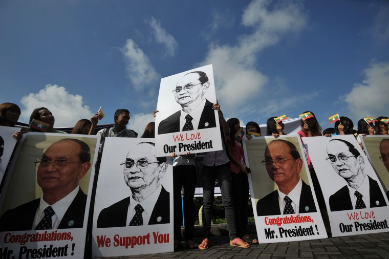 Supporters hold pictures of Myanmar president Thein Sein as they welcome him at Yangon International Airport upon his return from a landmark tour of the U.S. on October 1, 2012. (Soe Than Win/AFP/Getty Images)