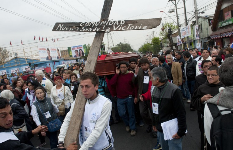 "People take part in the funeral of French priest Pierre Dubois in Santiago, on October 1, 2012. Dubois, who lived in the church of ""Nuestra Senora de la Victoria"" in southern Santiago's La Victoria slum, which was emblematic of the struggle against the dictatorship of Augusto Pinochet (1973-1990), died on September 28 at the age of 80. (Claudio Santana/AFP/Getty Images)"