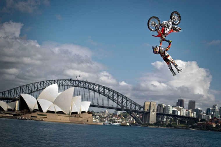 Josh Sheehan of Australia performs the opening jump in the Botanical Garden of Sydney in front of the Harbour Bridge and the Opera House to announce the final stage of the Red Bull X-Fighters World Tour on Cockatoo Island. (Sebastian Marko / Red Bull/AFP/Getty Images)