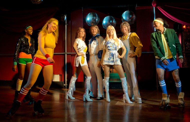 "Rollerskater Vilte Burneikaite (2nd L) skates around waxwork models of Swedish pop group 'Abba' at a roller disco in London. The wax models of Agnetha, Anni-Fird, Benny and Bjorn were dressed in replica outfits worn in their 1975 hit ""SOS"". The figures will take up residence in Madame Tussauds before going on a world tour including Vienna, Berlin, Amsterdam and Blackpool. Each figure cost GBP 150,000 (187,666 Euros) and took four months to create. (Adrian Dennis/AFP/Getty Images)"