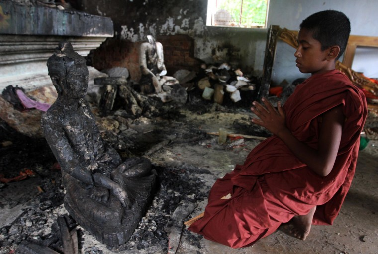A Buddhist monk prays in a burnt temple in Cox's Bazar, some 396 kilometres (246 miles) from the capital Dhaka. Bangladesh police said they had arrested nearly 300 people after Muslim mobs attacked temples and houses in what Buddhist leaders described as the worst violence against the community since independence. (STR/AFP/Getty Images)