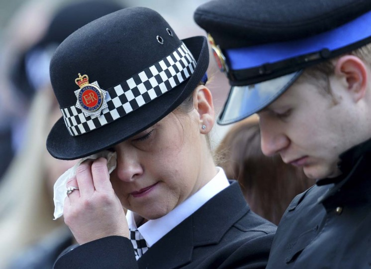 A police officer wipes away her tears as she listens to the funeral service of murdered British policewoman Fiona Bone outside Manchester Cathedral in north-west England. PC Nicola Hughes, 23, and PC Fiona Bone, 32, were killed in a gun and grenade attack as they responded to what they thought was a routine burglary call in Tameside, Greater Manchester, northwestern England, on September 18, 2012. (Andrew Yates/Getty Images)