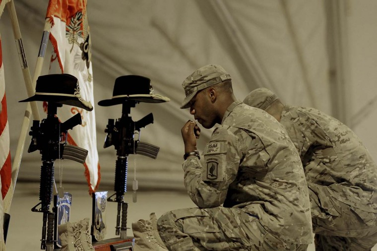 US Army soldiers attached to the 1st Squadron (Airborne) ,91st U.S Cavalry Regiment 173d Airborne Brigade Combat Team soldiers pay their respects by the boots, gun, cap and dog-tags of US army SSG Orion N. Sparks and SGT Jon Athan A. Gollnitz during a memorial ceremony in their honour at Forward Operating Base (FOB) Shank near Puli Alam in Logar Province, in Afghanistan. (Munir uz Zaman/Getty Images)