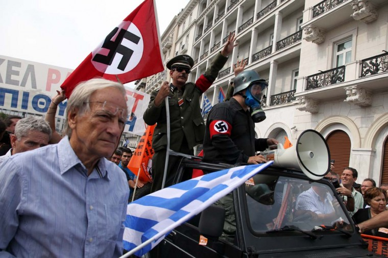 Demonstrators in mock Nazi garb ride in a vehicle in Athens during a demonstration against the vist of the German Chancellor Angela Merkel on October 9, 2012. (Max Gyselinck/AFP/Getty Images)