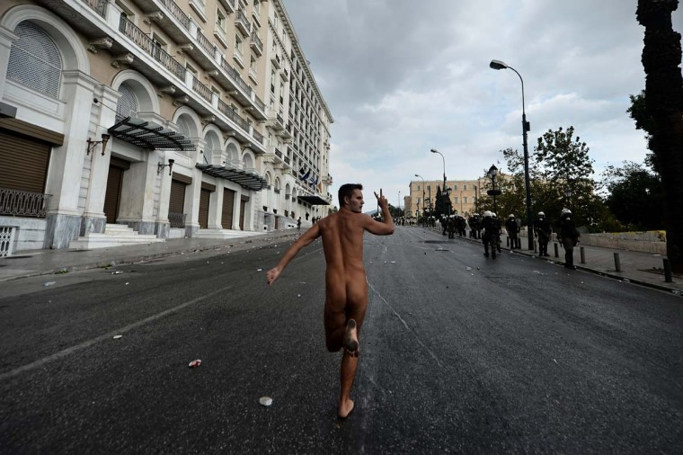 A naked demonstrator flashes the victory sign while running in Athens during a demonstration against the visit of the German Chancellor Angela Merkel on October 9, 2012. Athens went into security lock-down for Merkel's landmark visit, an austerity hate figure in Greece, whose arrival was greeted by union and opposition party protests. (Aris Messinis/AFP/Getty Images)