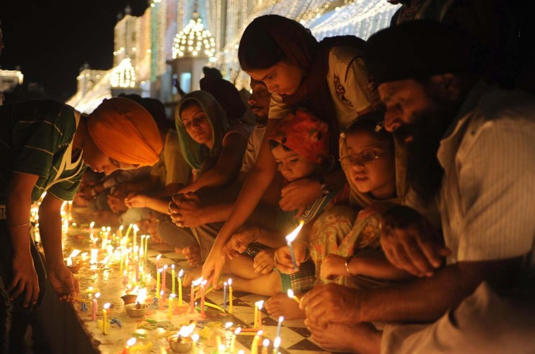 Indian Sikh devotees light candles at the illuminated Sikh Shrine Golden Temple, for the anniversary of the fourth Sikh Guru Ramdass, in Amritsar on October 9, 2012. (Narinder Nanu/AFP/Getty Images)