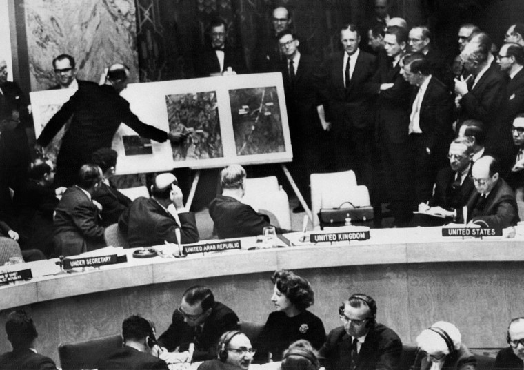 A U.S. administration official shows aerial views of a Cuban medium-range missile base as U.S. ambassador to the United Nations Adlai Stevension, right, describes the photos to members of the United Nations Security Council on Oct. 25, 1962. (File photo/AFP/Getty Images)