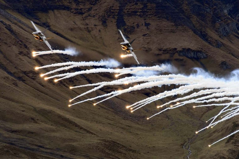 Two F/A-18 Hornet fighter aircraft of the Swiss Air Force release flares during a flight demonstration of the Swiss Air Force over Axalp in the Bernese Oberland. (Fabrice Cofrin/ AFP/Getty Images)