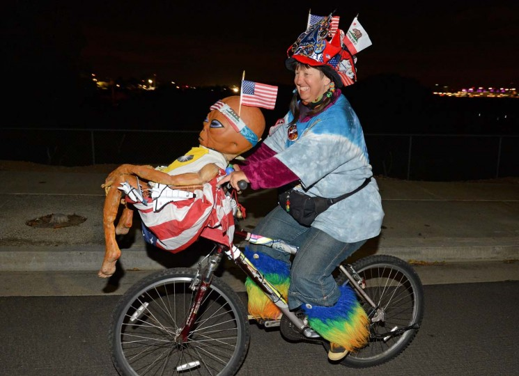 Space shuttle fan Vivian Robinson rides her bicycle covered in shuttle memorabilia, American flags and a alien doll,outside Los Angeles International Airport (LAX) as she waits to see Space Shuttle Endeavour, in the early morning hours in Los Angeles, California. The Space Shuttle began its journey from LAX to its permenant home in Los Angeles, in the early morning hours Oct 12, 2012. Over the next two days, the 170,000-pound (77,272 kg) shuttle will travel at no more than 2 mph (3.2 km per hour) along a 12-mile (19km) route from LAX to it's final home at the California Science Center. NASA Space Shuttle Program ended in 2011 after 30 years and 135 missions.(Robyn Beck/AFP/Getty Images)