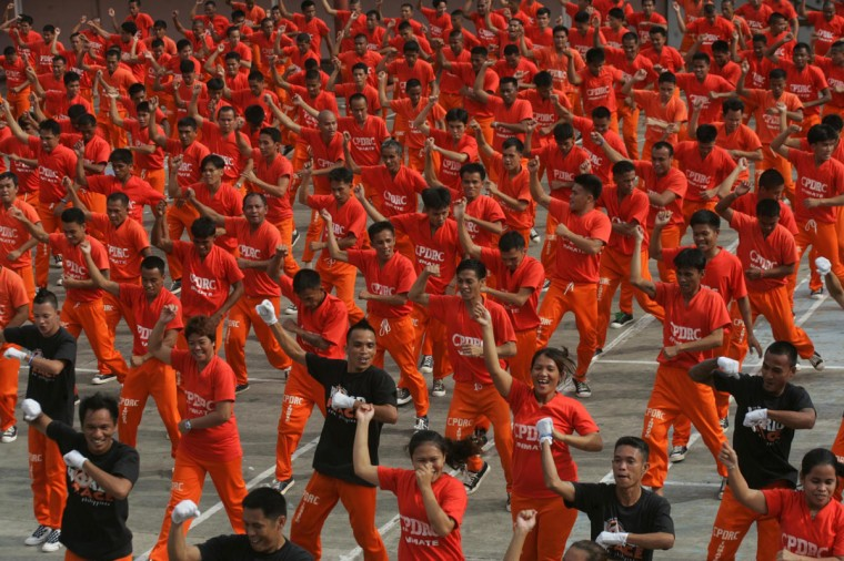 """Inmates from the Cebu City provincial jail dance the worldwide hit 'Gangnam Style' in Cebu City. Dressed in tangerine jump suits, the roughly 1,500 convicted murderers, rapists and other inmates perform """"Gangnam Style"""" to entertain visitors and tourists amd also have helped boost their morale while also making them Internet sensations. (STR/AFP/Getty Images)"""