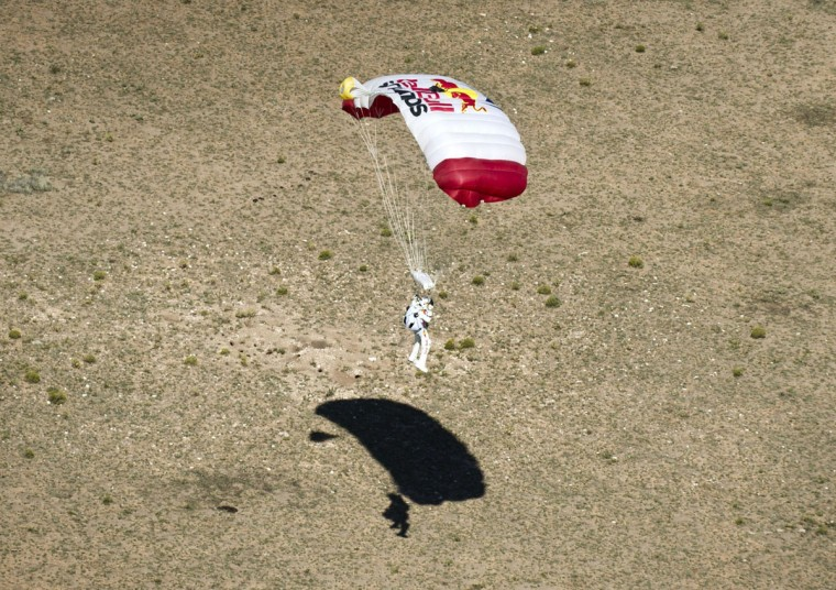 Pilot Felix Baumgartner of Austria lands in the desert after successfully completing the final manned flight for Red Bull Stratos in Roswell, New Mexico. The Austrian daredevil became the first man to break the sound barrier in a record-shattering freefall jump from the edge of space, organizers said. The 43-year-old leapt from a capsule more than 24 miles (39 kilometers) above the Earth, reaching a speed of 706 miles per hour (1,135 km/h) before opening his red and white parachute and floating down to the New Mexico desert. (Pedrag Vuckovic/AFP photo)
