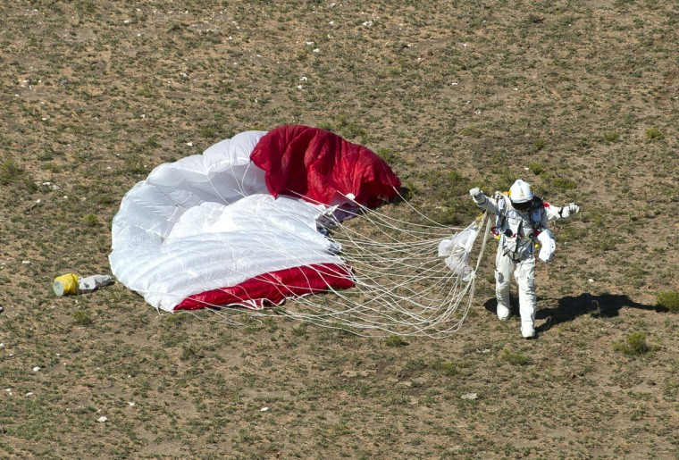 Pilot Felix Baumgartner of Austria celebrates upon landing in the desert after successfully completing the final manned flight for Red Bull Stratos in Roswell, New Mexico. The Austrian daredevil became the first man to break the sound barrier in a record-shattering freefall jump from the edge of space, organizers said. The 43-year-old leapt from a capsule more than 24 miles (39 kilometers) above the Earth, reaching a speed of 706 miles per hour (1,135 km/h) before opening his red and white parachute and floating down to the New Mexico desert. (Pedrag Vuckovic/AFP photo)