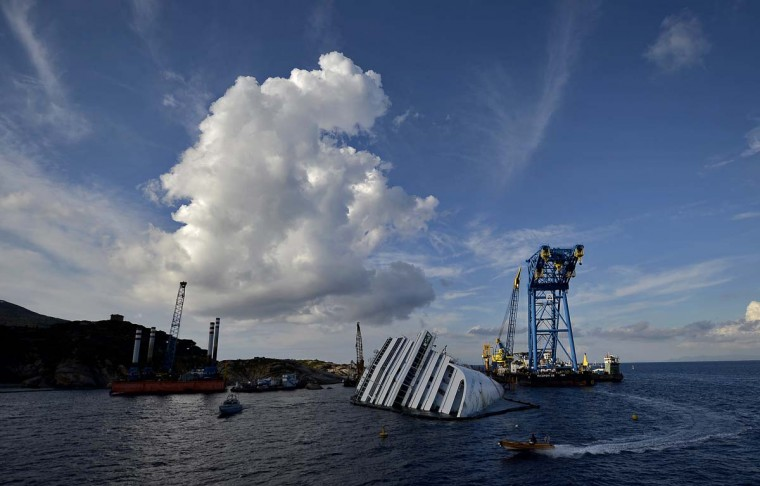 The Costa Concordia cruise ship lays near the harbor of Giglio Porto on October 14, 2012. An Italian court will begin hearings on October 15 to determine who should stand trial for a cruise ship disaster that left 32 people dead, amid accusations of safety breaches and fatal delays. (Filippo Monteforte/AFP/Getty Images)
