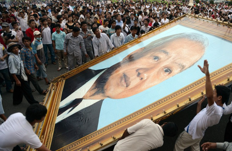 Cambodian people watch as workers install a portrait of the late former king Norodom Sihanouk in front of the Royal Palace in Phnom Penh. Grieving Cambodians wore black ribbons and flags flew at half-mast on October 16 as the nation mourned the death of revered ex-king Norodom Sihanouk and prepared for the return of his body from China. (Tang Chhin Sothy/AFP/Getty Images