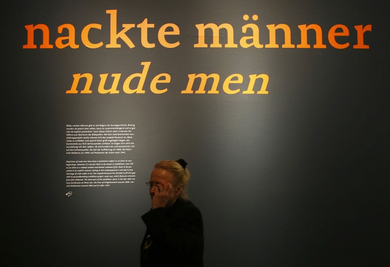 A woman walks past a wall with the title of the 'Nackte Maenner' (Nude Men) exhibition at the Leopold Museum in Vienna, on October 18, 2012. (Alexander Klein/AFP/Getty Images)