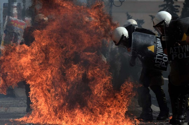 A firebomb explodes near riot police during clashes with demonstrators during a 24-hour strike in Athens. Greek riot police fired tear gas to disperse protesters at an anti-austerity rally in Athens held during a national general strike as EU leaders were to tackle the eurozone crisis at a summit. The protesters had broken through a police line outside luxury hotels on central Syntagma Square and scattered groups of youths later attacked police with stones and firebombs, an AFP reporter said. (Aris Messini/Getty Images)