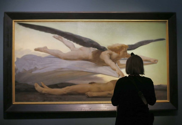A woman looks at an artwork by William Bouguereau, entitled 'Equality before Death,' as part of the 'Nackte Maenner' (Nude men) exhibition at the Leopold Museum in Vienna, on October 18, 2012. (Alexander Klein/AFP/Getty Images)