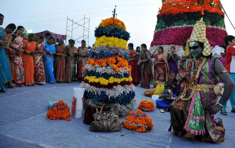 Indian artist B. Nooka Raju (R) dressed as Hindu God Lord Venkateshwara joins Indian Hindu women devotees as they perform rituals with floral displays as they celebrate the 'Bathukamma' or 'Life Giver' Festival in Hyderabad on October 22, 2012. (Noah Seela/AFP/Getty Images)