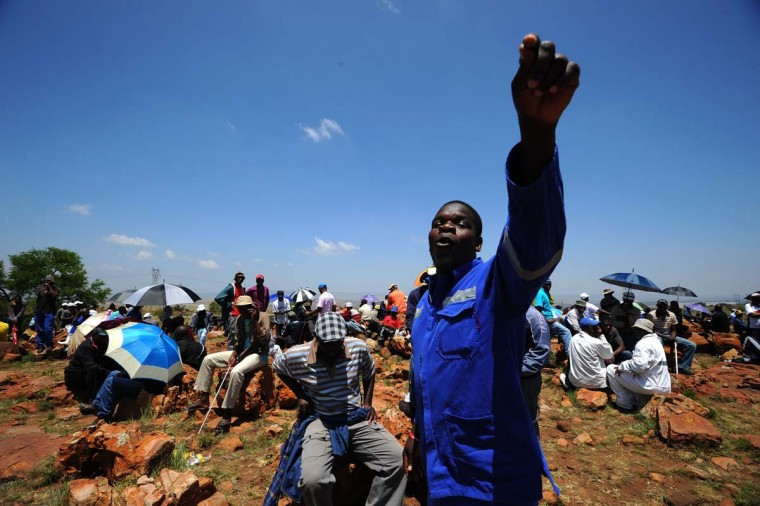 A striking miner calls others to go on with the protest on the hill at the AngloGold Ashanti mine in Carletonville on October 22, 2012. AngloGold Ashanti, the world's third-largest gold producer, became today the latest mining firm to issue an ultimatum to striking workers in South Africa that they must return to the mines or be dismissed. (Alexander Joe/AFP/Getty Images)
