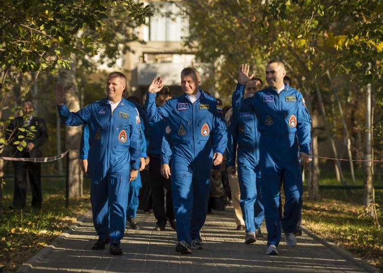 October 23, 2012: Expedition 33/34 crew members, Flight Engineer Kevin Ford of NASA, left, Soyuz Commander Oleg Novitskiy, and Flight Engineer Evgeny Tarelkin of ROSCOSMOS, right, depart the Cosmonaut Hotel to head to another building across the Baikonur Cosmodrome where they will suit-up for their soyuz launch in Baikonur, Kazakhstan. (NASA/Bill Ingalls/AFP/Getty Images)