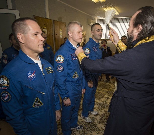 October 23, 2012: Expedition 33/34 crew members, Flight Engineer Kevin Ford of NASA (L), Soyuz Commander Oleg Novitskiy, and Flight Engineer Evgeny Tarelkin of ROSCOSMOS (R) receive the traditional blessing from a Russian Orthodox priest at the Cosmonaut Hotel on the morning of their Soyuz launch to the International Space Station in Baikonur, Kazakhstan. (NASA/Bill Ingalls/AFP/Getty Images)